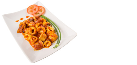 sambal: Malaysian dish of fried squid with hot and spicy sambal or chili gravy with scallion and tomatoes on white plate.