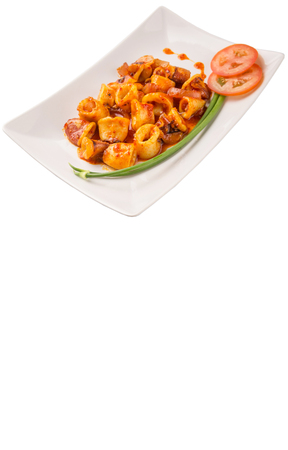 scallion: Malaysian dish of fried squid with hot and spicy sambal or chili gravy with scallion and tomatoes on white plate.