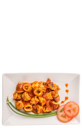 sambal: Malaysian dish of fried squid with hot and spicy sambal ot chili gravy with scallion and tomatoes on white plate.