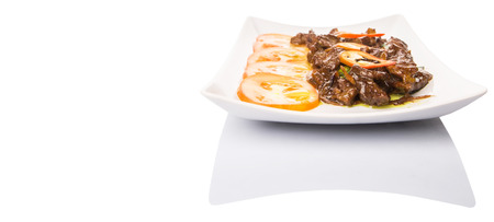 plating: Malaysian dish stir fried beef meat with oyster sauce and tomato slices in white plate