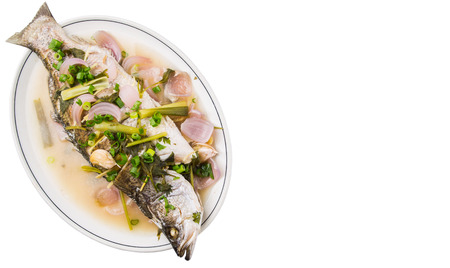 plating: Malaysian dish of sweet and sour steamed barramundi or Asian bass fish on white plate