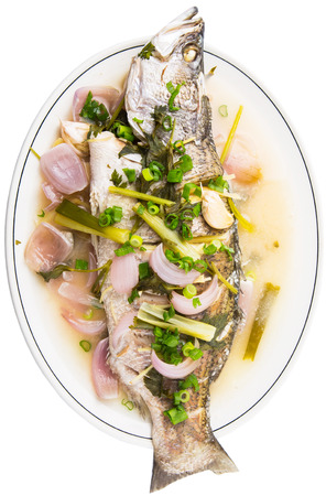 barramundi: Malaysian dish of sweet and sour steamed barramundi or Asian bass fish on white plate