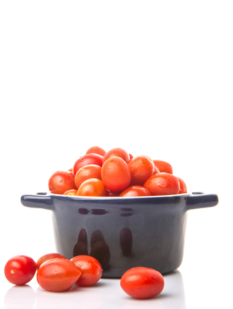 sized: Bite sized red cherry grape tomato in blue pot over white background