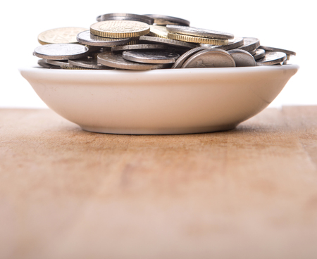 accumulate: Malaysian coins in a white bowl over wooden surface
