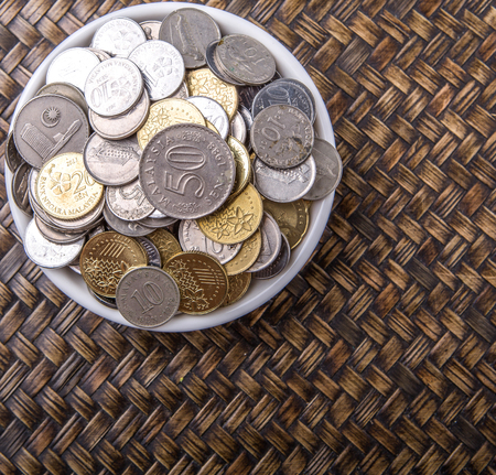 Malaysian coins in a white bowl over wicker background photo