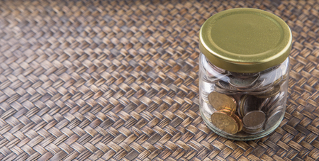 accumulate: Malaysian coins in a mason jar over wicker background