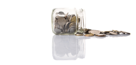 accumulate: Malaysian coins in a mason jar over white background