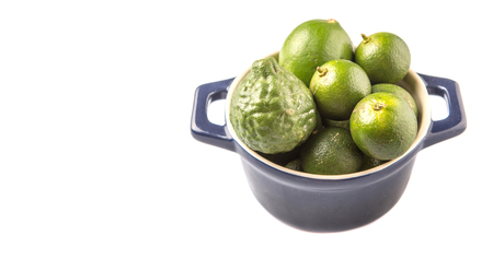 acidity: Lime makrut or kaffir lime and calamansi in blue pot over white background