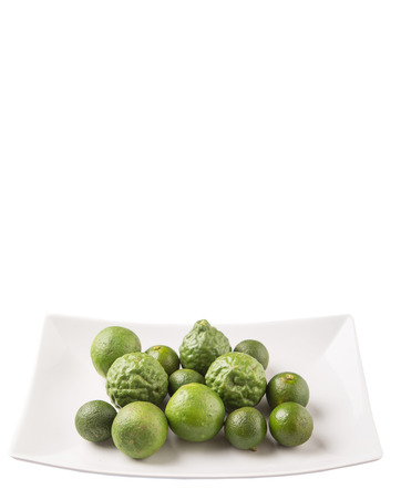 acidity: Lime makrut or kaffir lime and calamansi on white plate over white background