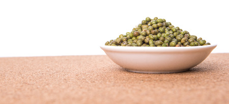Mung beans in white bowl on cork board background photo