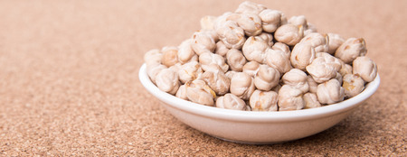 Chickpeas in white bowl on cork board photo
