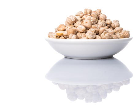 Chickpeas in a white bowl over white background