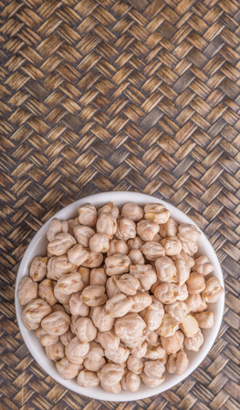 Chickpeas in white bowl on wicker background photo