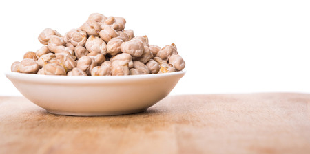 Chickpeas in a white bowl on wooden board photo