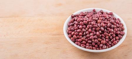 aduki bean: Red adzuki beans in white bowl over wooden background