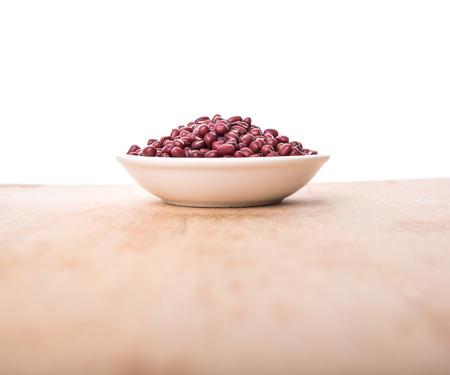 adzuki: Red adzuki beans in white bowl over wooden background