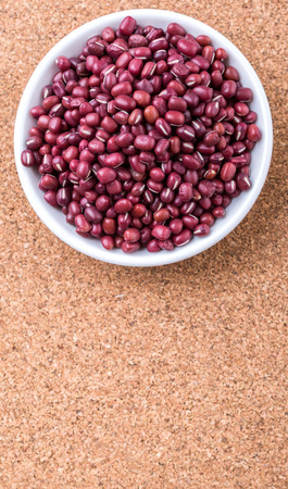 aduki bean: Red adzuki beans in white bowl over cork board background
