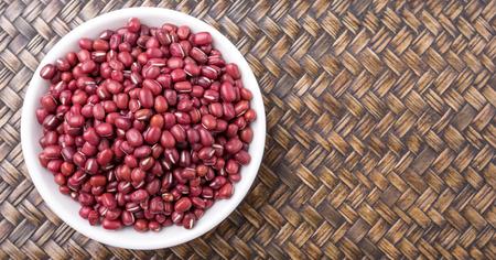 aduki bean: Red adzuki beans in white bowl over wicker background Stock Photo