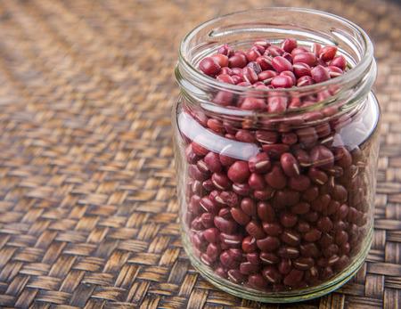 aduki bean: Red adzuki beans in a mason jar over wicker background Stock Photo