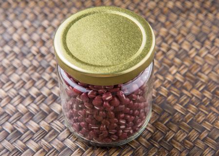 adzuki: Red adzuki beans in a mason jar over wicker background Stock Photo