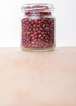 aduki bean: Red adzuki beans in a mason jar over wooden background
