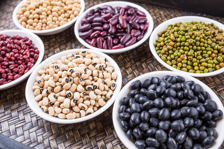 Black eye peas mung bean adzuki beans soy beans black beans and red kidney beans in white bowl on wicker tray Banque d'images