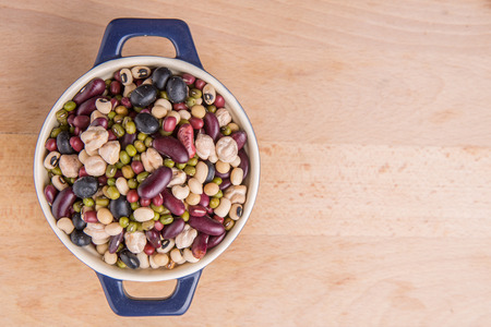 aduki bean: Mix beans of black eye peas mung bean adzuki beans soy beans black beans and red kidney beans in a blue pot over wooden background Stock Photo