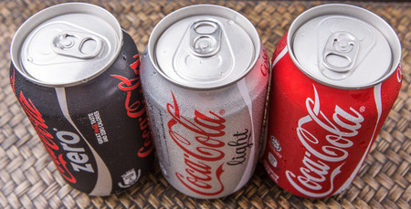 cola canette: PUTRAJAYA MALAISIE 28 JUIN 2015. canettes de Coca-Cola sur fond osier. Boissons de Coca-Cola sont produits et fabriqu�s par La CocaCola soci�t� une soci�t� am�ricaine de boisson multinationale.