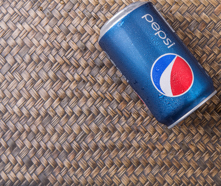 famous industries: PUTRAJAYA MALAYSIA  JUNE 28TH 2015. Pepsi can on wicker background Pepsi is a carbonated soft drink produced and manufactured by PepsiCo Inc. an American multinational food and beverage company.