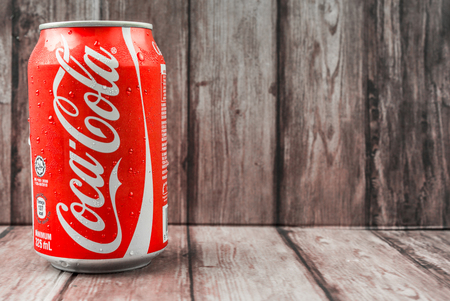 famous industries: PUTRAJAYA MALAYSIA  JUNE 28TH 2015. Coca Cola can on weathered wood. Coca Cola drinks are produced and manufactured by The CocaCola Company an American multinational beverage corporation.