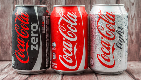 cola canette: PUTRAJAYA MALAYSIA  JUNE 28TH 2015. Coca Cola cans on weathered wood. Coca Cola drinks are produced and manufactured by The CocaCola Company an American multinational beverage corporation.