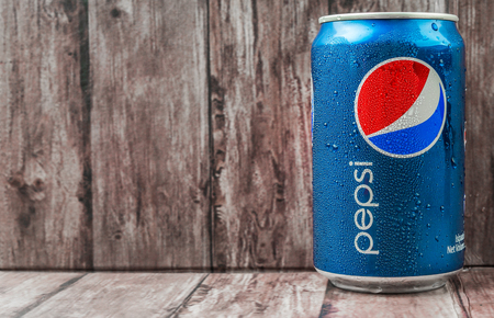 famous industries: PUTRAJAYA MALAYSIA  JUNE 28TH 2015. Pepsi can on weathered wood. Pepsi is a carbonated soft drink produced and manufactured by PepsiCo Inc. an American multinational food and beverage company.