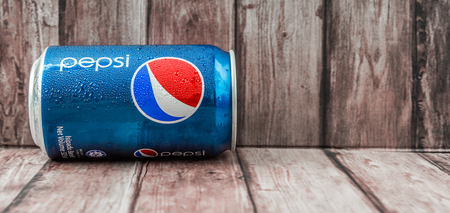 famous industries: PUTRAJAYA, MALAYSIA - JUNE 28TH, 2015. Pepsi can on weathered wood. Pepsi is a carbonated soft drink produced and manufactured by PepsiCo Inc. an American multinational food and beverage company. Editorial