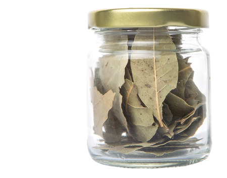Dried bay leaves herbs in a mason jar over white background
