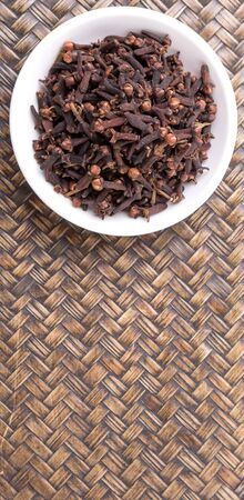clove: Clove spices in a white bowl on wicker background