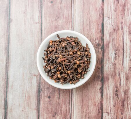 clove: Clove spices in white bowl over weathered wooden background