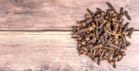 Clove spices over weathered wooden background Archivio Fotografico