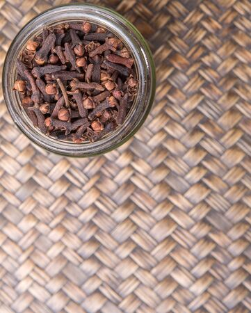 clove plant: Clove spices in a mason jar over wicker background