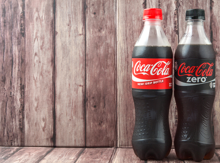 cola bottle: PUTRAJAYA, MALAYSIA - JULY 2ND, 2015. Coca Cola bottle on weathered wood. Coca Cola drinks are produced and manufactured by The Coca-Cola Company, an American multinational beverage corporation. Editorial