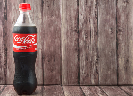 cola bottle: PUTRAJAYA, MALAYSIA - JULY 2ND, 2015. Coca Cola bottle on weathered wood. Coca Cola drinks are produced and manufactured by The Coca-Cola Company, an American multinational beverage corporation