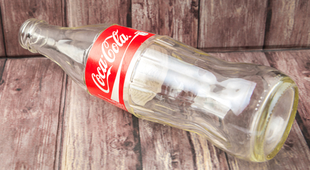 multinational: PUTRAJAYA, MALAYSIA - JULY 2ND, 2015. Empty Coca Cola bottle. Coca Cola drinks are produced and manufactured by The Coca-Cola Company, an American multinational beverage corporation.