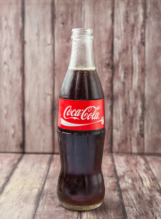 cola bottle: PUTRAJAYA, MALAYSIA - JULY 2ND, 2015. Coca Cola bottle on weathered wood. Coca Cola drinks are produced and manufactured by The Coca-Cola Company, an American multinational beverage corporation. Editoriali