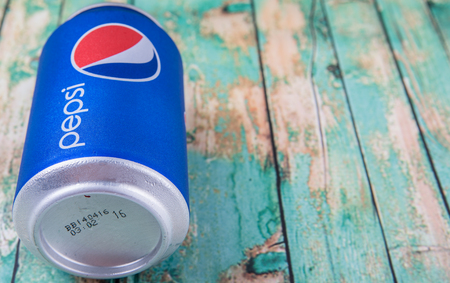famous industries: PUTRAJAYA, MALAYSIA - JULY 5TH, 2015. Pepsi can on weathered wood. Pepsi is a carbonated soft drink produced and manufactured by PepsiCo Inc. an American multinational food and beverage company. Editorial