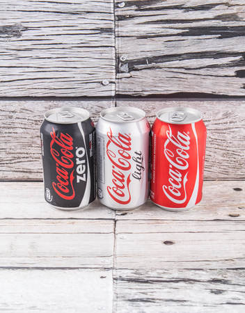 cola canette: PUTRAJAYA, Malaisie - 5 JUILLET 2015. canettes de Coca-Cola sur fond de bois vieilli. Boissons de Coca-Cola sont produits et fabriqués par The Coca-Cola Company, une société américaine de boisson multinationale. Éditoriale