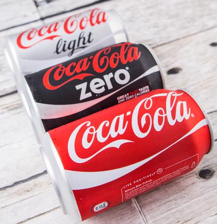 cola canette: PUTRAJAYA, Malaisie - 5 JUILLET 2015. canettes de Coca-Cola sur fond de bois vieilli. Boissons de Coca-Cola sont produits et fabriqu�s par The Coca-Cola Company, une soci�t� am�ricaine de boisson multinationale. �ditoriale