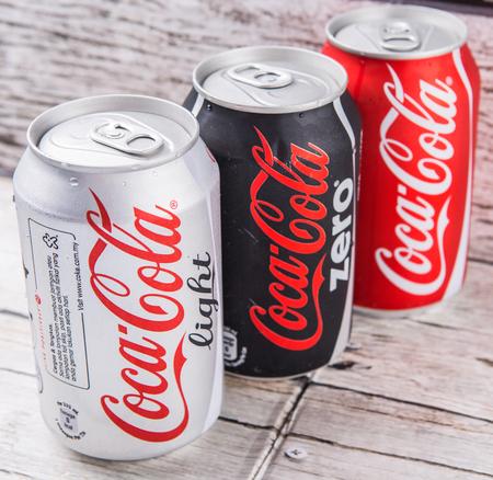 multinacional: Putrajaya, Malasia - el 5 de julio, 2015. latas de Coca Cola en el fondo de madera envejecida. Bebidas Coca Cola son producidos y fabricados por The Coca-Cola Company, una corporaci�n multinacional de bebidas de Am�rica.