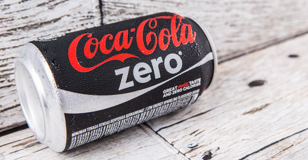 famous industries: PUTRAJAYA, MALAYSIA - JULY 5TH, 2015. Coca Cola Zero on weathered wood. Coca Cola drinks are produced and manufactured by The Coca-Cola Company, an American multinational beverage corporation. Editorial