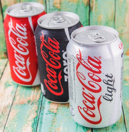 cola canette: PUTRAJAYA, MALAYSIA - JULY 5TH, 2015. Coca Cola cans on aged wooden background. Coca Cola drinks are produced and manufactured by The Coca-Cola Company, an American multinational beverage corporation. Éditoriale