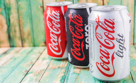 cola canette: PUTRAJAYA, MALAYSIA - JULY 5TH, 2015. Coca Cola cans on aged wooden background. Coca Cola drinks are produced and manufactured by The Coca-Cola Company, an American multinational beverage corporation. �ditoriale