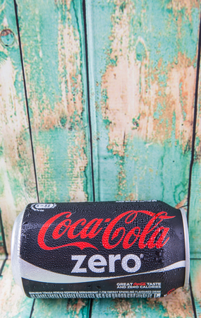 famous industries: PUTRAJAYA, MALAYSIA - JULY 5TH, 2015. Coca Cola Zero on weathered wood. Coca Cola drinks are produced and manufactured by The Coca-Cola Company, an American multinational beverage corporation Editorial